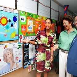 Simone Clarke-Cooper Assist. VP, Group Corporate Comm. Supreme Ventures Ltd., Sonita Abrahams Executive Director RISE Life management Services and Vitus Evans Executive Director BGLC viewing posters.