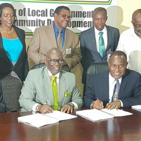 L-R front row: Hugh Burton, HDB Construction Ltd., HM McKenzie, Portmore Mayor Leon Thomas, CEO, Portmore MC, Kerry Chambers. Mp for Southern St. Catherine Fitz Jackson (extreme right) observes the signing