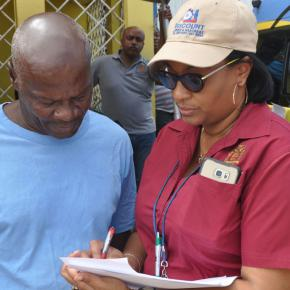 Regional Manager of Property Tax Compliance, Wendye Peterkin (right) explains Property Tax Notices to a resident of Farm Heights