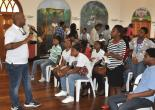 Councillor of the Spring Garden Division and Chairman of the Civic and Community Affairs Committee at the St. James Municipal Corporation, Dwight Crawford (left), addresses participants of the Youth Summer Employment Programme (YSEP) at an orientation exercise.