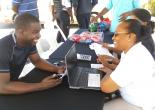 Regional Manager of Property Tax Compliance, Wendye Peterkin (seated, right),  engages former Junior Mayor of Montego Bay, Jerome Johnson at the Mobile Property Tax promotion in Meadows of Irwin, Montego Bay on June 23, 2018