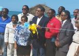 Tourism and Entertainment Minister, Hon. Dr. Wykeham McNeill (centre), cuts the ribbon to officially open the refurbished Burwood Beach in Falmouth, Trelawny.