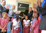 Minister of Agriculture, Labour and Social Security, Hon Derrick Kellier (right) is assisted by Minister of Education, the Hon. Rev. Ronald Thwaites (2nd left) as he cuts the ribbon to officially open the Falmouth Infant School Library on Friday May 15.