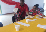 Councillor Trecia Harris-Smiley looks on while Mayor Freeman severs hot meal