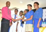 CEO of the St. James Municipal Corporation, Mr. Gerald Lee (left), presents students - (from left) Khalie Wray, Mikkaile Cardouza, Adrianna Dixson and Govind Girnami - of Mt. Alvernia Preparatory School with the 1st place winner's trophy after the school won the 10th Annual Disaster Awareness Quiz Competition Finals that were held on Tuesday, June 6, 2017 at the Montego Bay Cultural Centre. Parish Coordinator - Disaster Preparedness, Ms. Tamoy Sinclair (right) shares the moment.